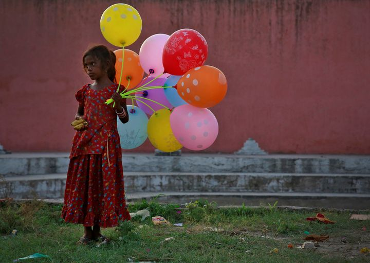 A young girl sells balloons by the Yamuna River on the last day of the Ganesh Chaturthi festival in Delhi, India, on Sept. 15