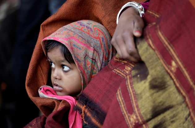 A little girl wrapped in a shawl waits along with her mother at a railway station in New Delhi, India,...