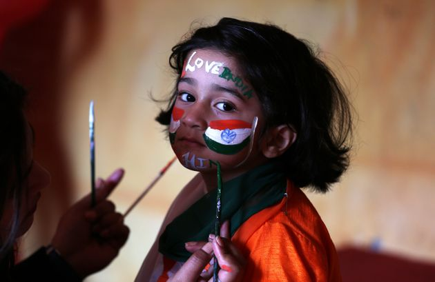 A school girl gets her face painted in the colors of India's national flag before taking part in the...