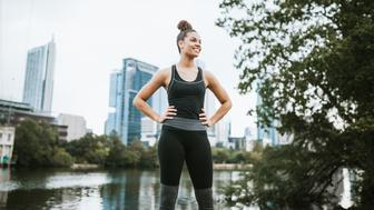 A young adult African American woman pauses on her morning run, downtown Austin, Texas and the Colorado river visible behind her.  She has a happy expression on her face, her hands confidently on her hips.  Horizontal image.
