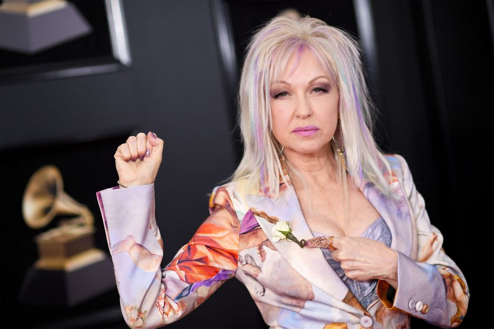 Recording artist Cyndi Laupershows off her white rose at the Grammy Awards.