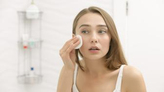 Focused beautiful young woman cleaning her skin with a cotton pad, looking at the mirror at home bathroom. Beauty, skin care concept, lifestyle