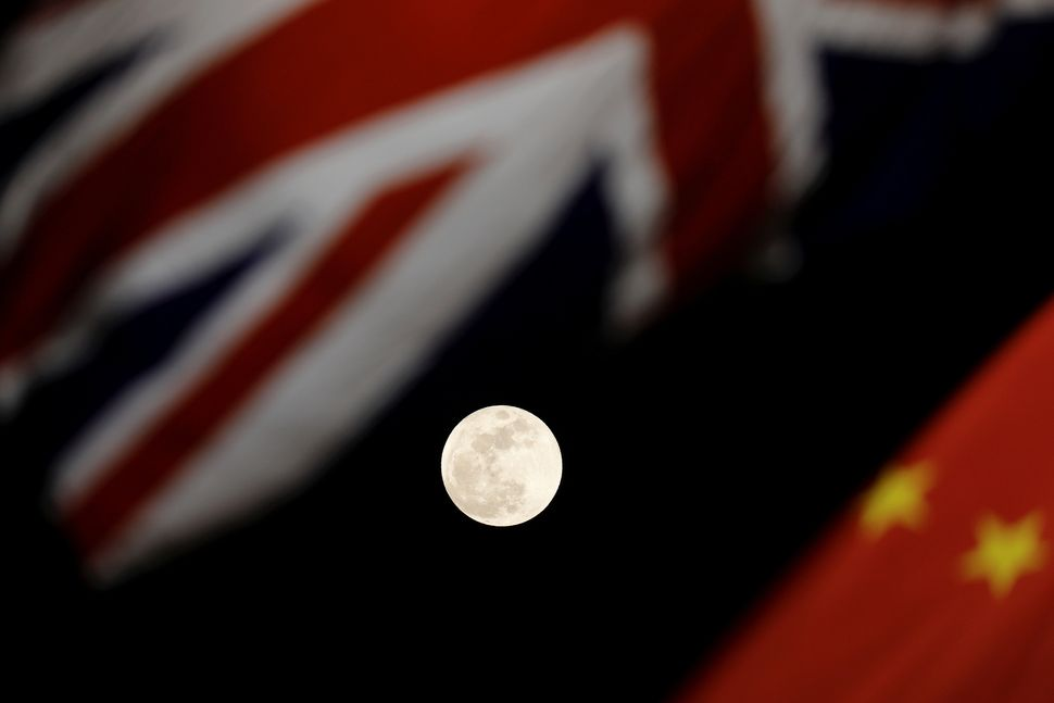 The moon is seen between British and Chinese flags raised at Tiananmen Square in Beijing as British Prime Minister Theresa Ma