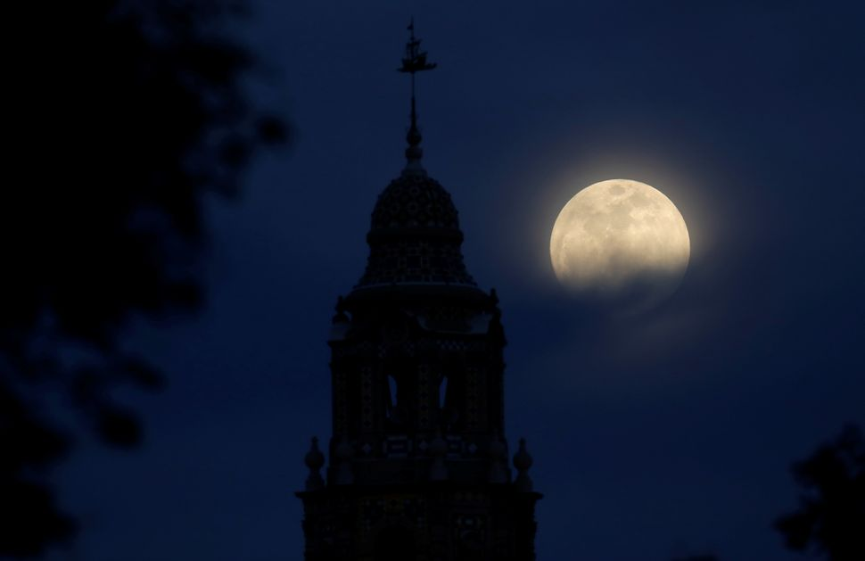 The moon rises over Balboa Park's California Tower in San Diego.