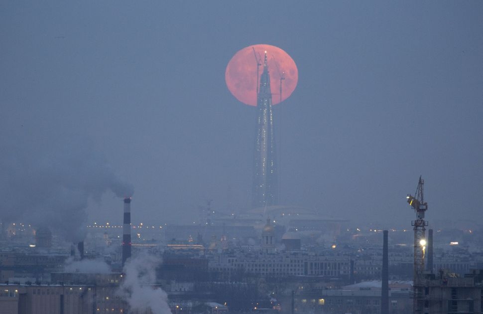 The moon is seen behind the under business tower Lakhta Center, which is under construction.