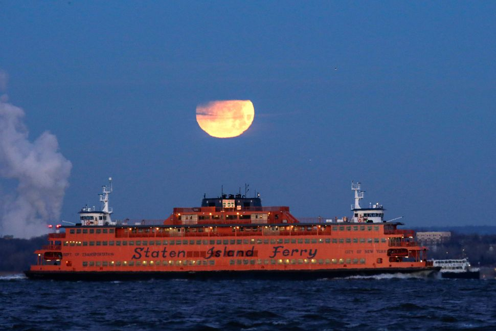 The moon sets behind the Staten Island Ferry, seen from Brooklyn.