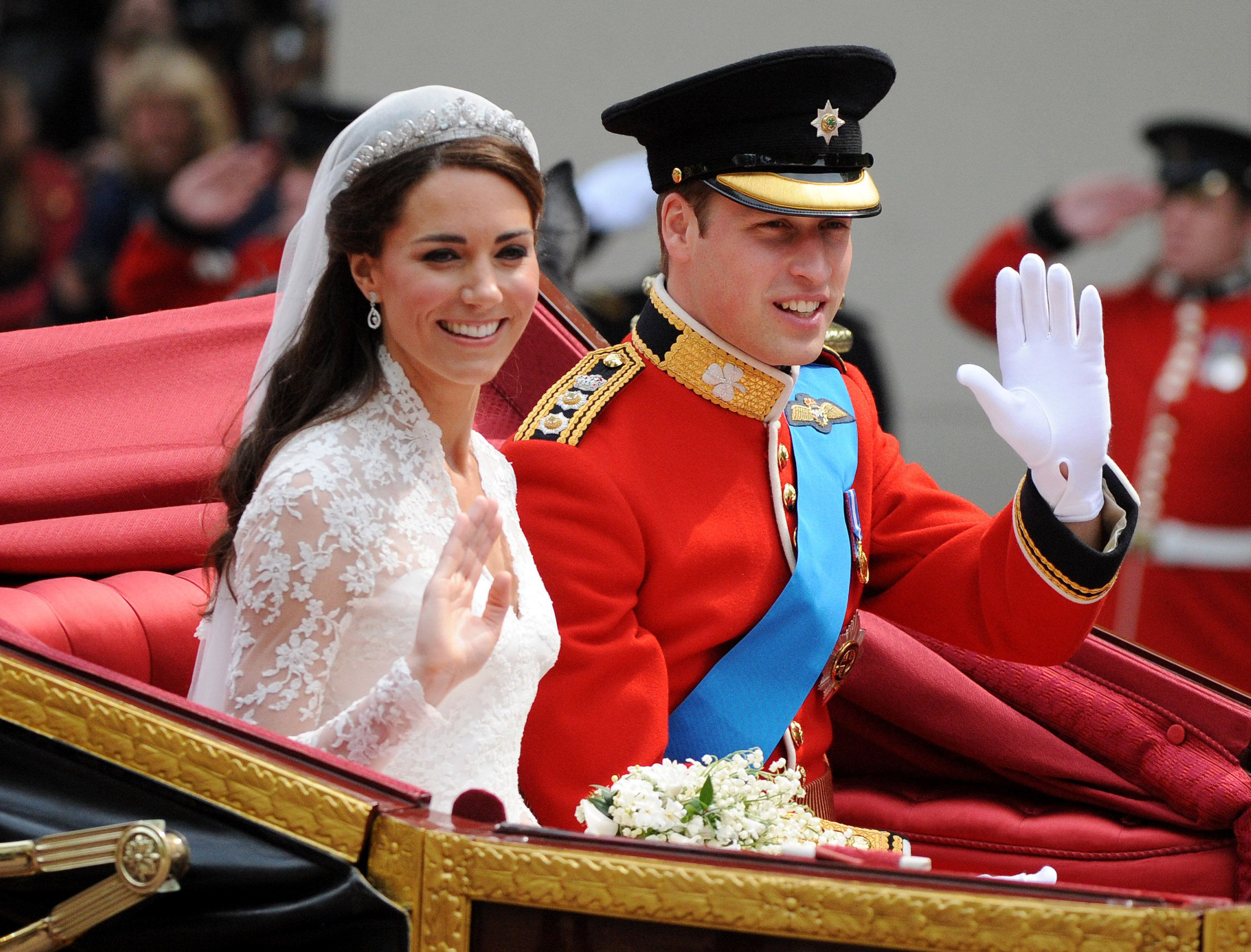 Catherine Middleton and Prince William drive down the Mall in an open carriage on their way to Buckingham...