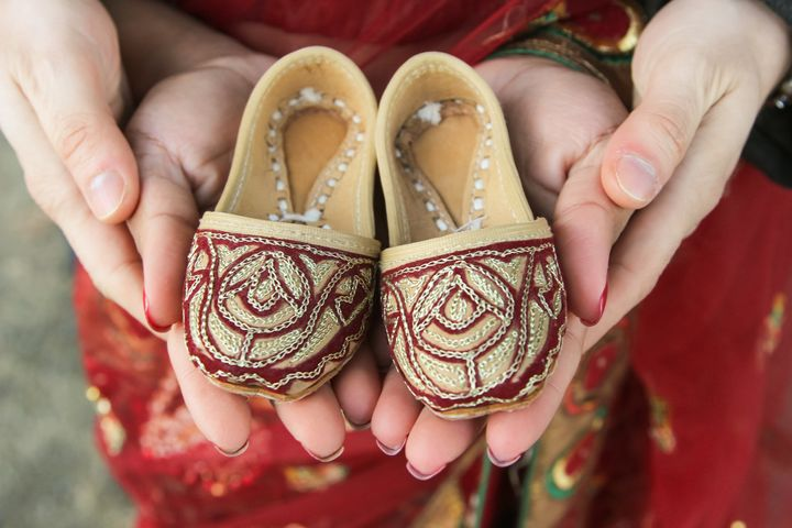 Sherine and Alessandro Valverde hold juttis, traditional Indian dress shoes, during their maternity shoot.