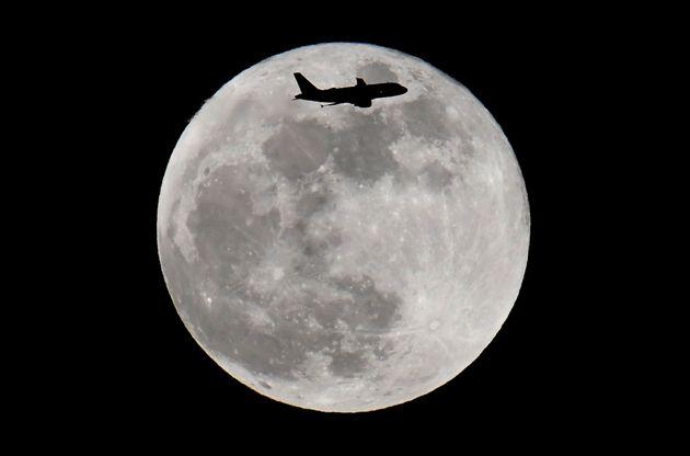 月の前を飛ぶ旅客機