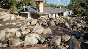 Boulders surround a mud-filled property after a mudslide in Montecito, California, U.S. January 12, 2018.  REUTERS/ Kyle Grillot