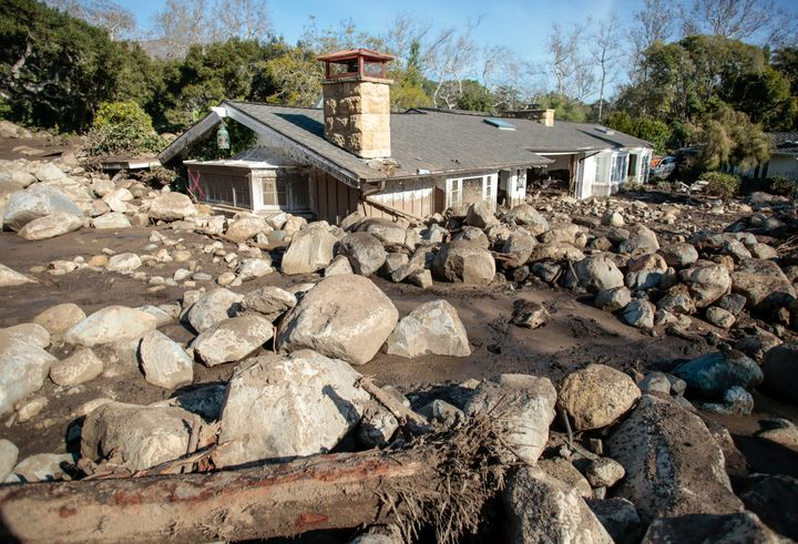 Boulders surround a mud-filled property after a mudslide in Montecito.