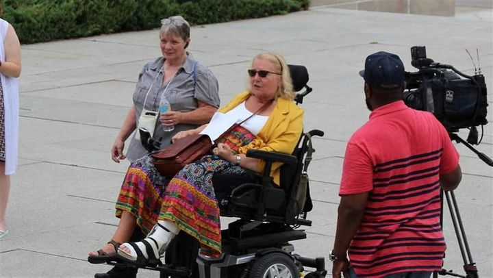 Kathy Hoell, second from left, joins another activist to advocate for disability rights at the state Capitol in Lincoln. Hoel