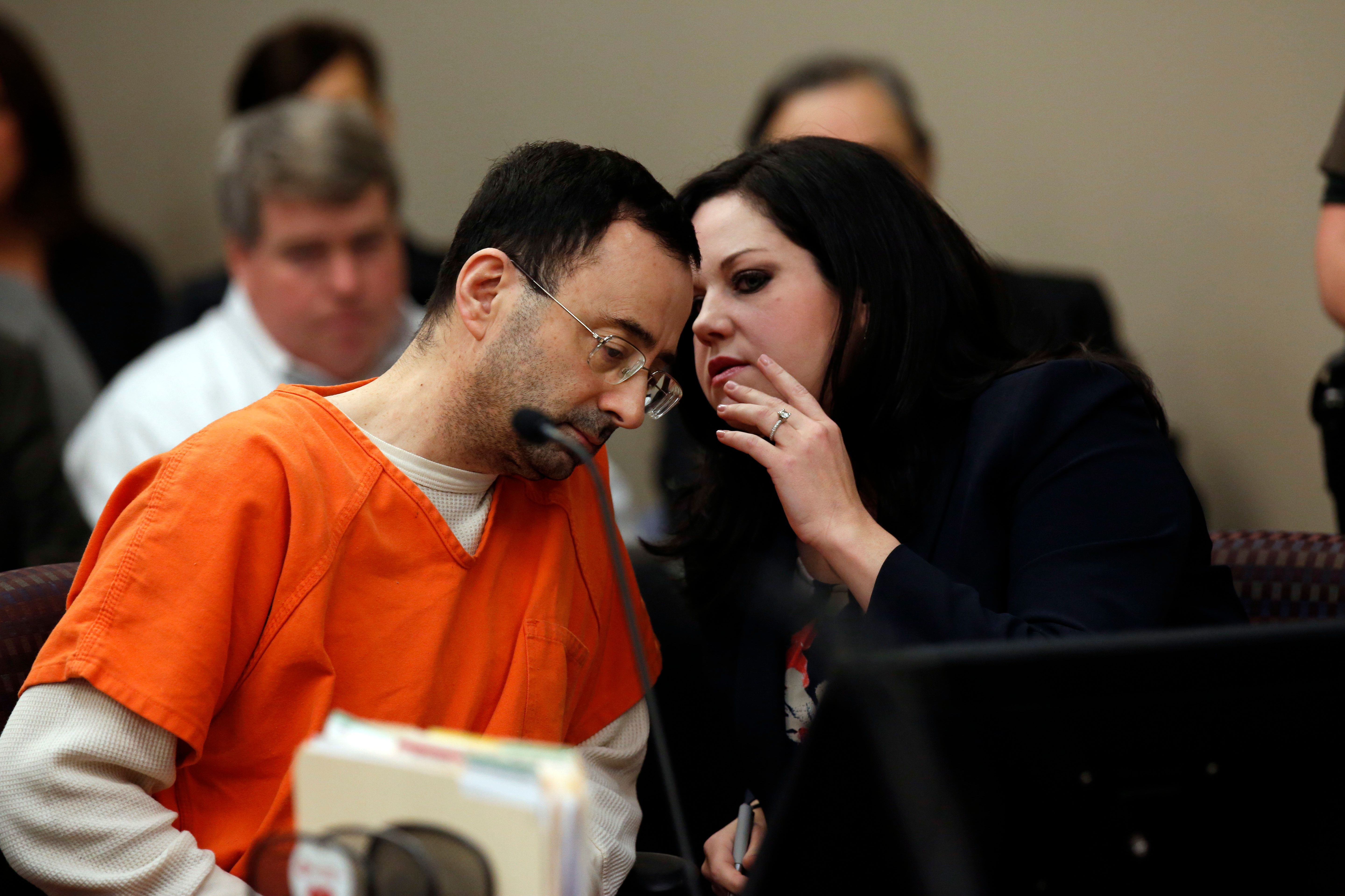 Former Michigan State University and USA Gymnastics doctor Larry Nassar (L) listens to defense attorney Shannon Smith (R) in Ingham County Circuit Court on November 22, 2017 in Lansing, Michigan. Former USA Gymnastics team doctor Lawrence (Larry) Nassar, accused of molesting dozens of female athletes over several decades, on Wednesday pleaded guilty to multiple counts of criminal sexual conduct. Nassar -- who was involved with USA Gymnastics for nearly three decades and worked with the country's gymnasts at four separate Olympic Games -- could face at least 25 years in prison on the charges brought in Michigan.  / AFP PHOTO / JEFF KOWALSKY        (Photo credit should read JEFF KOWALSKY/AFP/Getty Images)