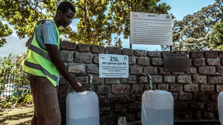 Cape Town residents fill water bottles after waiting in line at Newlands Brewery Spring Water Point on Tuesday.