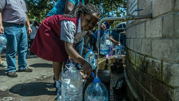 A little girl helps fill water bottles at Newlands Brewery Spring Water Point in Cape Town on