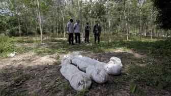 ATTENTION EDITORS - VISUAL COVERAGE OF SCENES OF INJURY OR DEATH Policemen take notes behind human remains retrieved from a mass grave at a rubber plantation near a mountain in Thailand's southern Songkhla province May 6, 2015. Authorities in Thailand have dug up the bodies of six suspected Rohingya migrants from Myanmar at a rubber plantation near a mountain where a mass grave was found at the weekend, the military said on Wednesday. The discovery was made in Thailand's Songkhla province near the country's border with Malaysia around 4 km from the site where the 26 bodies were found a few days ago. REUTERS/Surapan Boonthanom