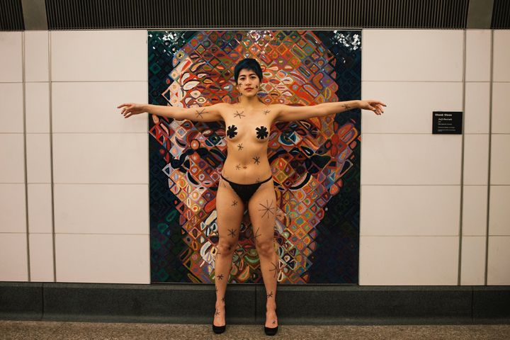 Performance artist Emma Sulkowicz protests Chuck Close's artwork in the 86th Street subway station in New York by providing&n
