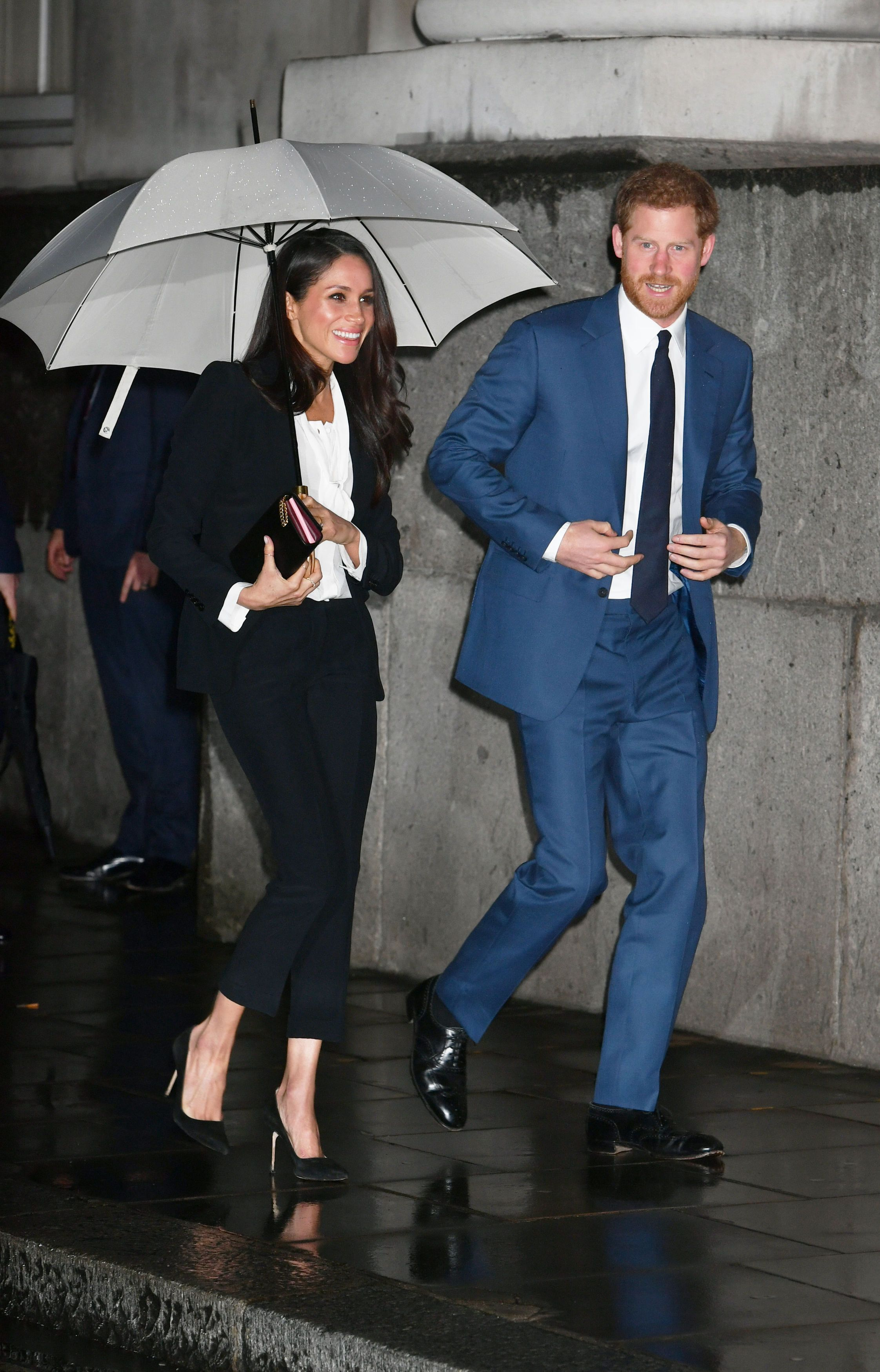 Prince Harry opted for a navy suit with a matching blue tie. They carried this season's hottest accessory: an umbrella.