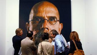 MIAMI BEACH, FL - DECEMBER 03:  People look a painting by Chuck Close at Art Basel Miami Beach December 3, 2008 in Miami Beach, Florida. The event is the sister event of Switzerland's Art Basel. Art Basel Miami Beach combines an international selection of top galleries with an exciting program of special exhibitions and events.  (Photo by Joe Raedle/Getty Images)