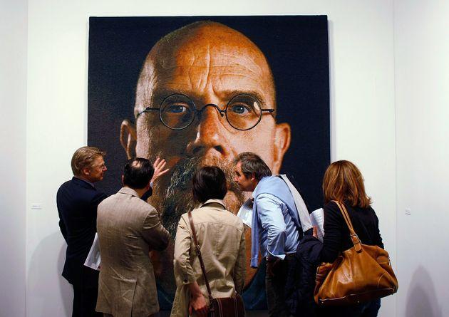 An art tour group studiesa painting by Chuck Close at Art Basel Miami Beach in