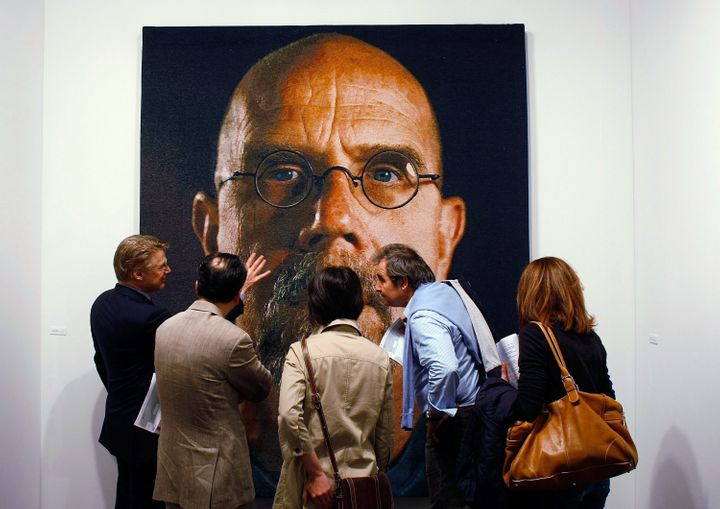 An art tour group studies a painting by Chuck Close at Art Basel Miami Beach in 2008.