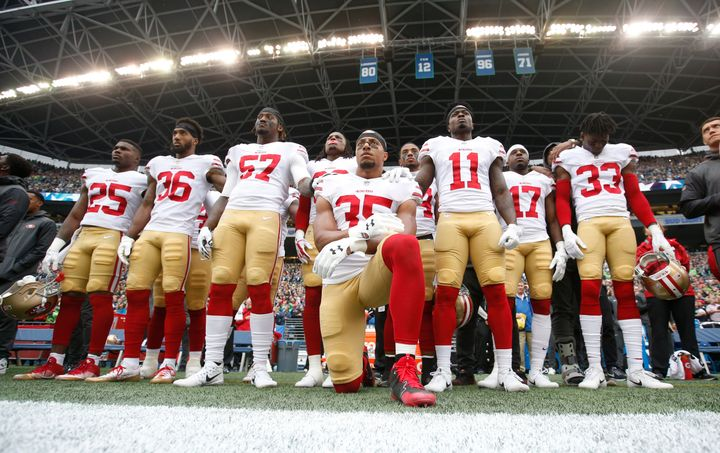 Eric Reid of the San Francisco 49ers kneels during the national anthem with his teammates' support, prior to a