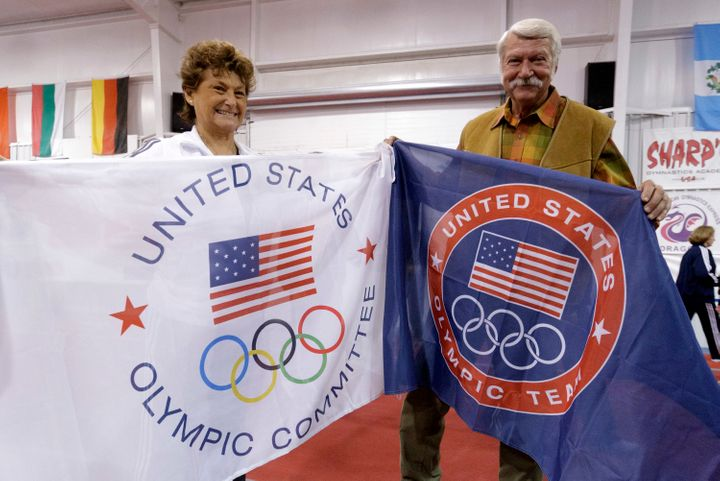 "Martha and Bela Karolyi display banners at their gym, ""the Ranch,"" to celebrate its being named an official training sit"
