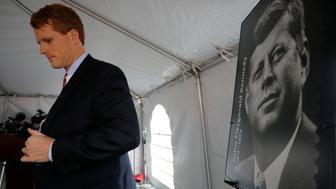 U.S. Congressman Joe Kennedy III stands next to a poster of a stamp of featuring his great-uncle, U.S. President John F. Kennedy, during ceremonies on the 100th anniversary of the birth of President Kennedy outside the home where he was born in Brookline, Massachusetts, U.S., May 29, 2017.   REUTERS/Brian Snyder