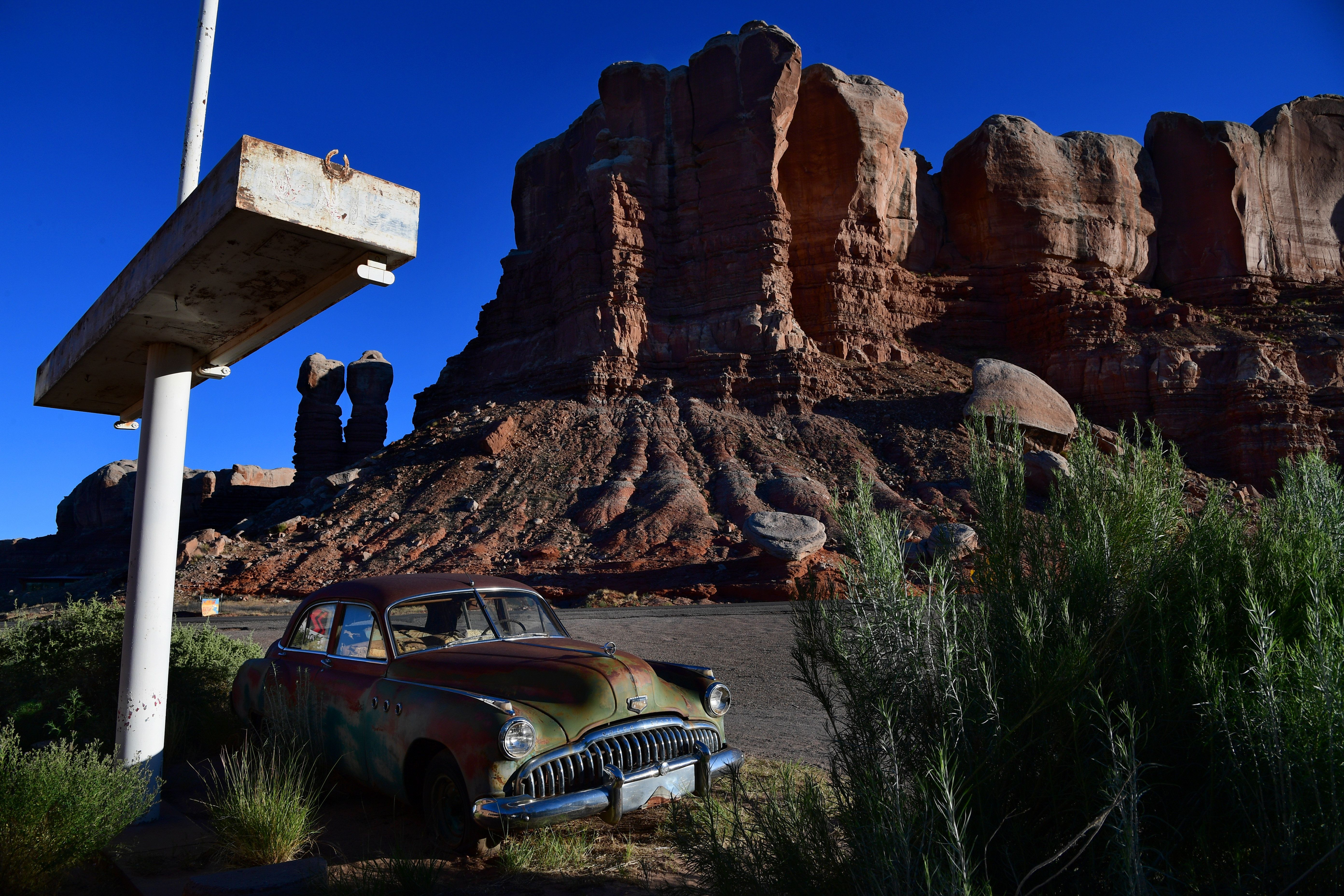 BLUFF, UT - JUNE 13: A former gas station turned into an art gallery called Cow Canyon Trading Post features a vintage Buick Super Eight with a backdrop of Twin Rocks, part of Bears Ears National Monument seen June 13, 2017 in Bluff, UT.    (Photo by Katherine Frey/The Washington Post via Getty Images)