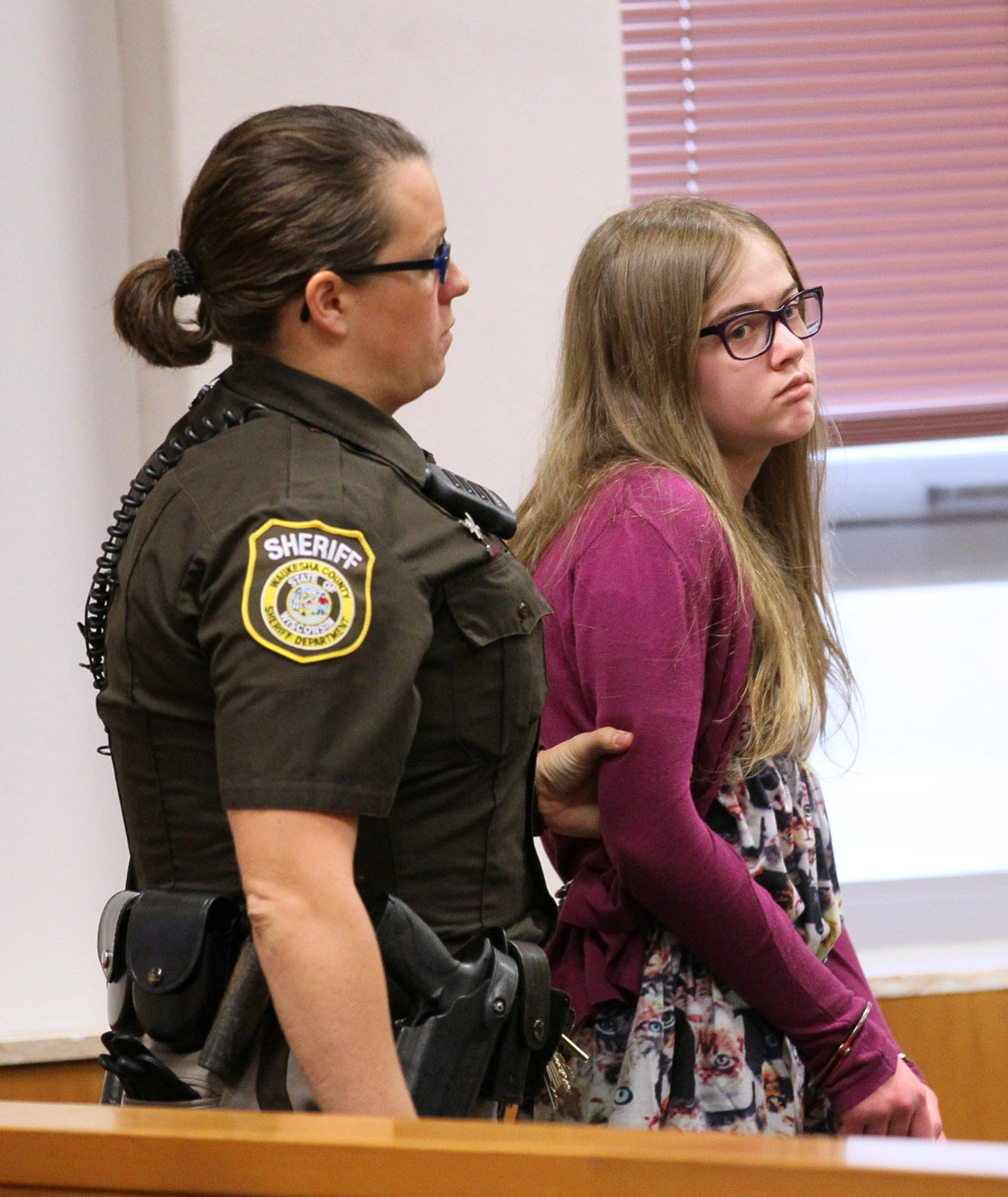 A sheriff's deputy brings Morgan Geyser into court on Aug. 21, 2015.