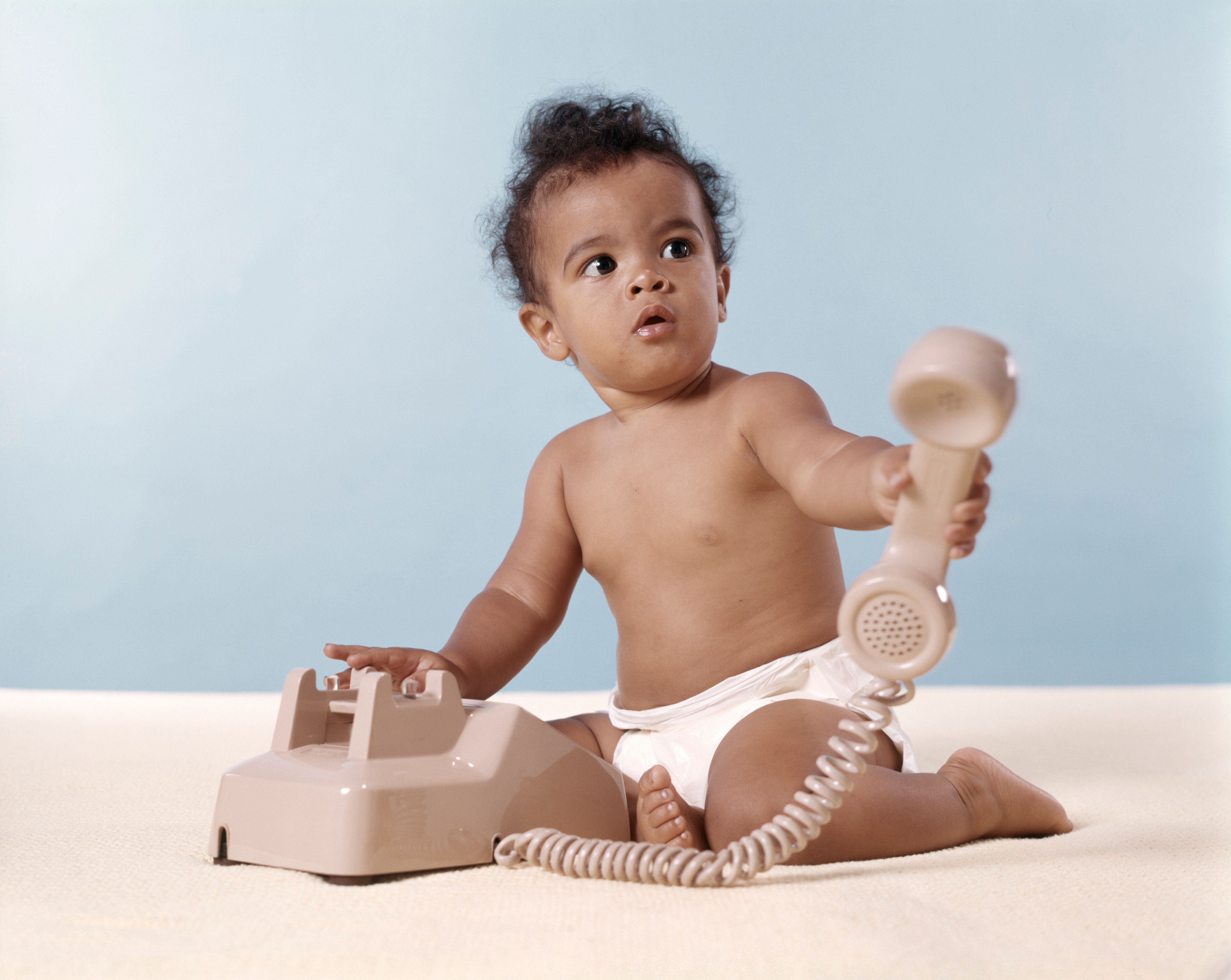 UNITED STATES - Circa 1960s:  African-American Baby In Diaper Holding Telephone.
