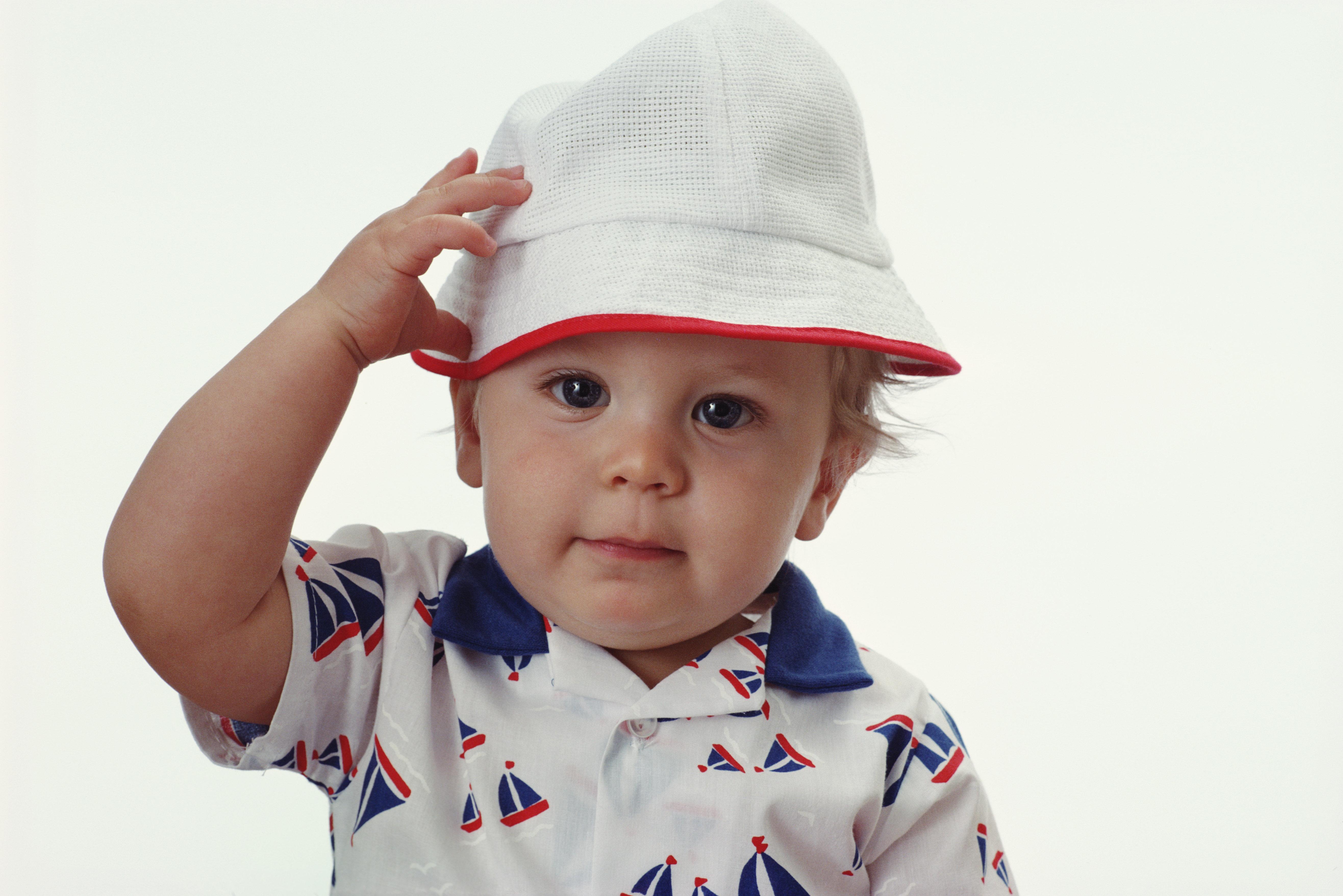 Baby boy (9-12 months) wearing hat, close-up, portrait