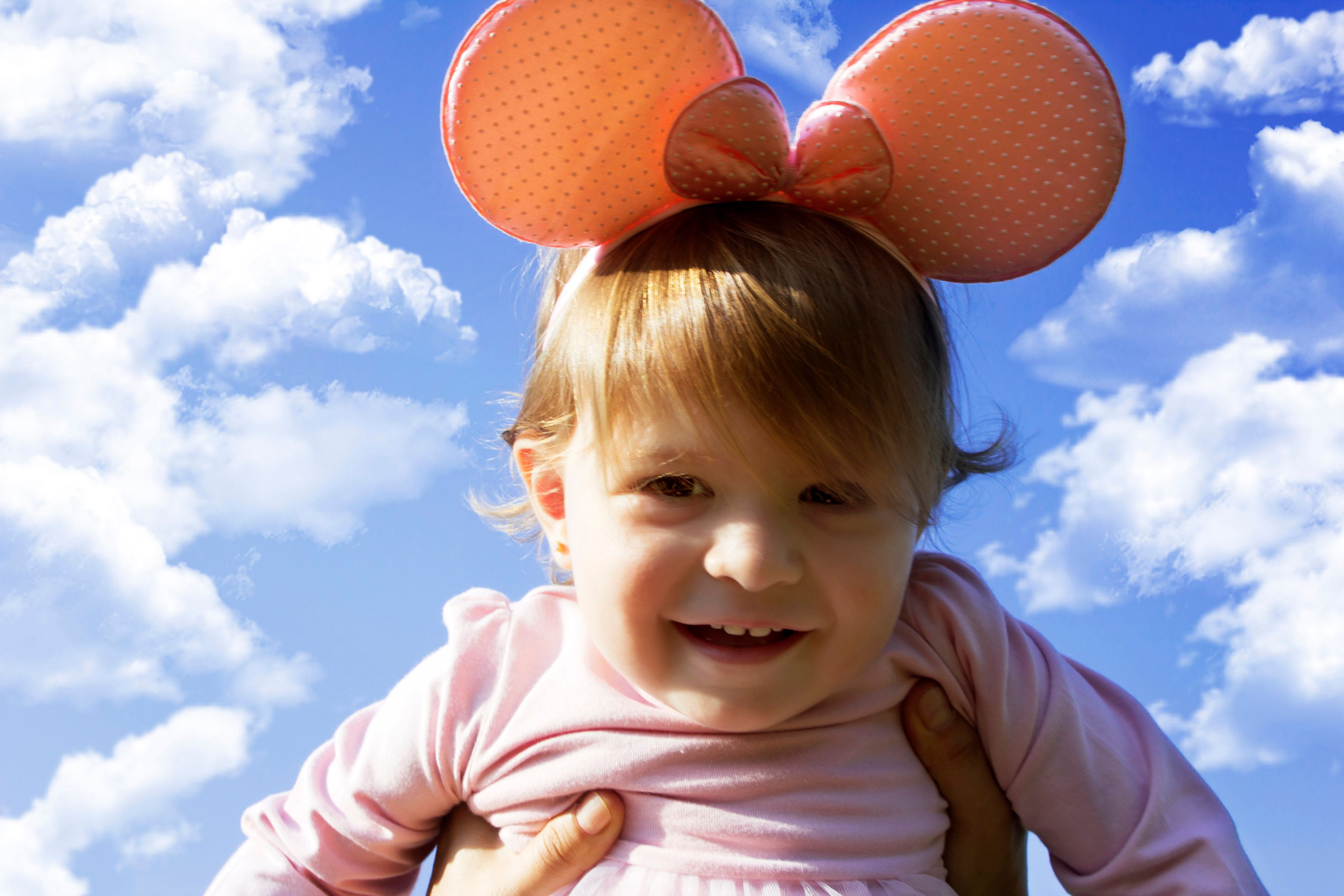 Portrait of little girl with mickey crown on the blue sky with clouds
