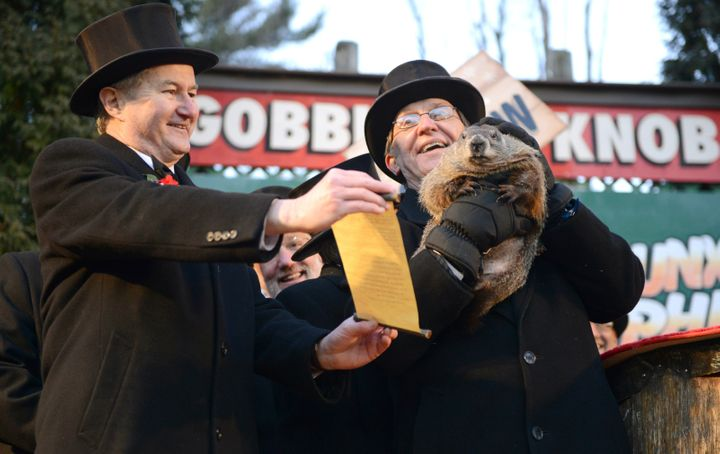 Groundhog Club Vice President Jeff Lundy, left, shares Punxsutawney Phil's prediction with co-handler Ron Ploucha at the 2016