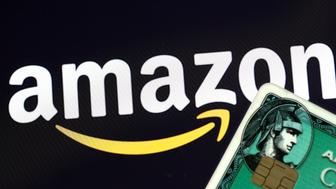 A n American Express credit card is held in front of an Amazon logo in this picture illustration taken September 6, 2017. REUTERS/Philippe Wojazer