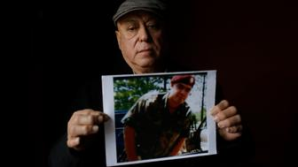 Miguel Perez poses as he holds a photo of his son Miguel Perez Jr., on April 4, 2017 in Chicago, Illinois. Perez Jr., an Army veteran is facing deportation after serving seven years in a state penitentiary on a drug charge. / AFP PHOTO / Joshua LOTT / TO GO WITH AFP STORY BY NOVA SAFO-'US military veterans deported after committing crimes'        (Photo credit should read JOSHUA LOTT/AFP/Getty Images)