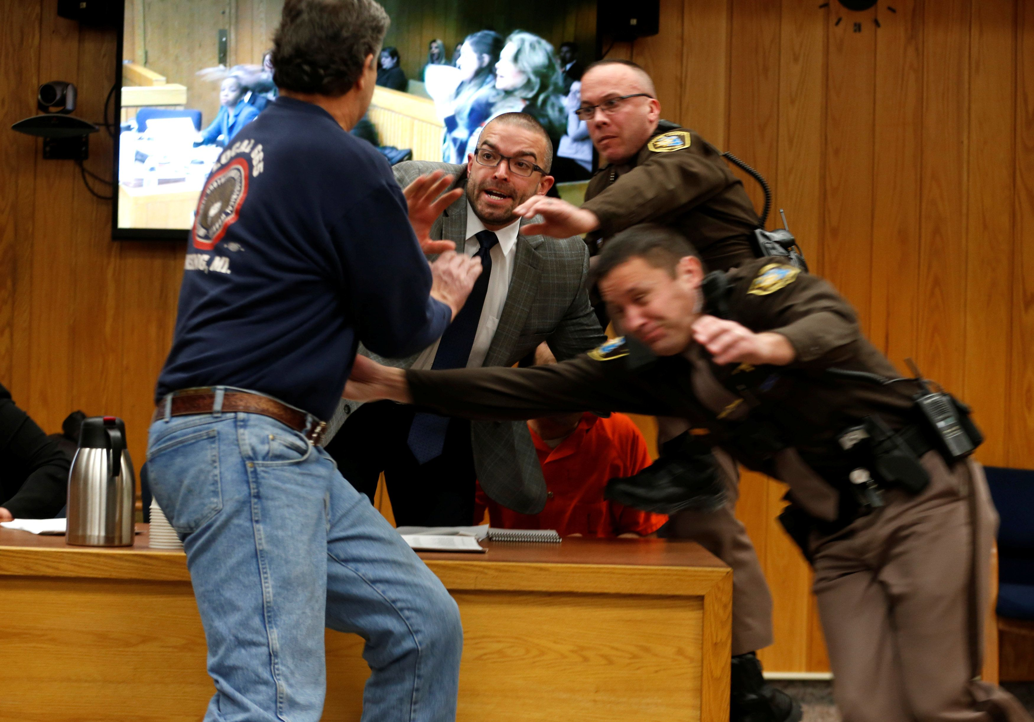 Randall Margraves, left, attempts to attack former USA Gymnastics doctor Larry Nassar (wearing orange)...