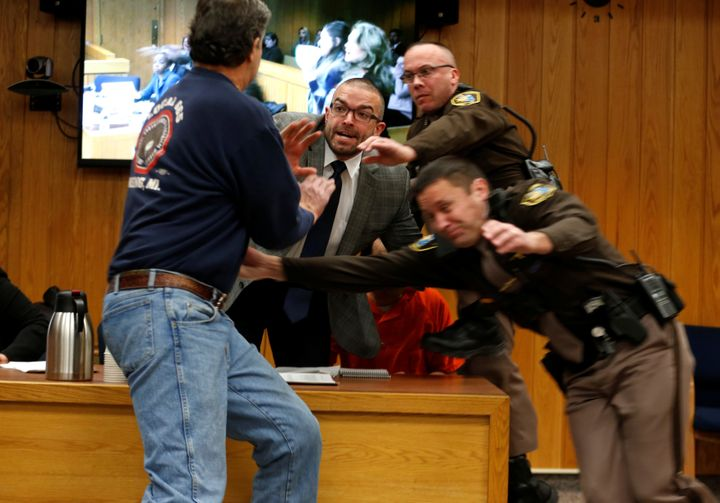 Randall Margraves, left, attempts to attack former USA Gymnastics doctor Larry Nassar (wearing orange) in court.