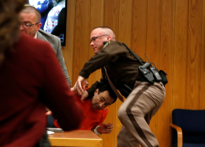 Nassar's attorney and a law enforcement officer deflect Margraves' attack.