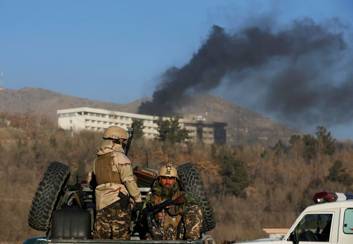 Afghan security forces look on as smoke rises from the Intercontinental Hotel in Kabul on Jan. 21, 2018.