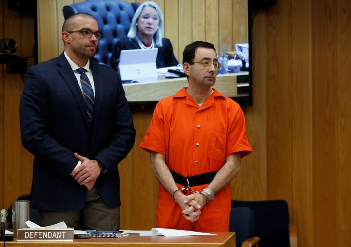 Larry Nassar stands with his attorney Matt Newburg as Judge Janice Cunningham (seen on screen) gives instructions during Nass