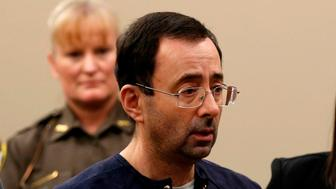 Former Michigan State University and USA Gymnastics doctor Larry Nassar (C) with defense attorneys  Matt Newberg (L) and Molly Blythe (R) during the sentencing phase in Ingham County Circuit Court on January 24, 2018 in Lansing, Michigan.  Disgraced former USA Gymnastics doctor Larry Nassar was sentenced to 40 to 175 years in prison on Wednesday for sexually abusing scores of young girls under the guise of medical treatment. 'I've just signed your death warrant,' Judge Rosemarie Aquilina said as she handed down the sentence after a week of gut-wrenching testimony by over 150 of Nassar's victims.  / AFP PHOTO / JEFF KOWALSKY        (Photo credit should read JEFF KOWALSKY/AFP/Getty Images)
