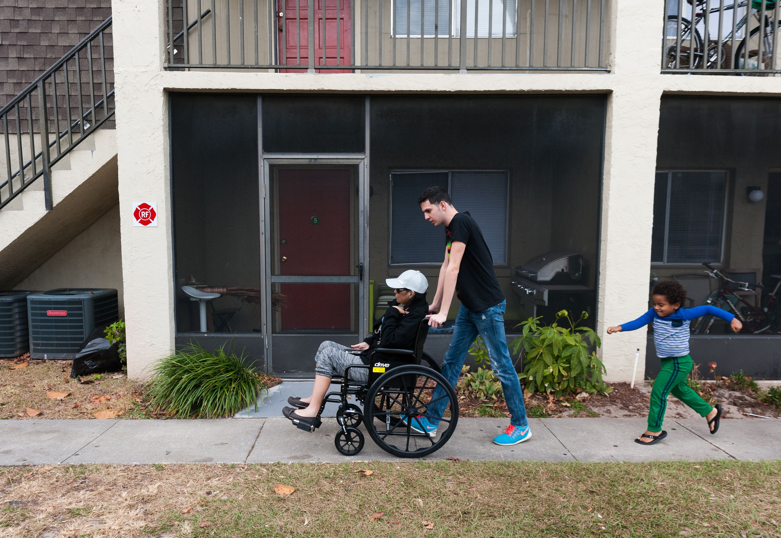 Jan Miguel pushes his mother, Mariluz, in a wheelchair on their way to get a ride to a doctor appointment. Jan Miguel's