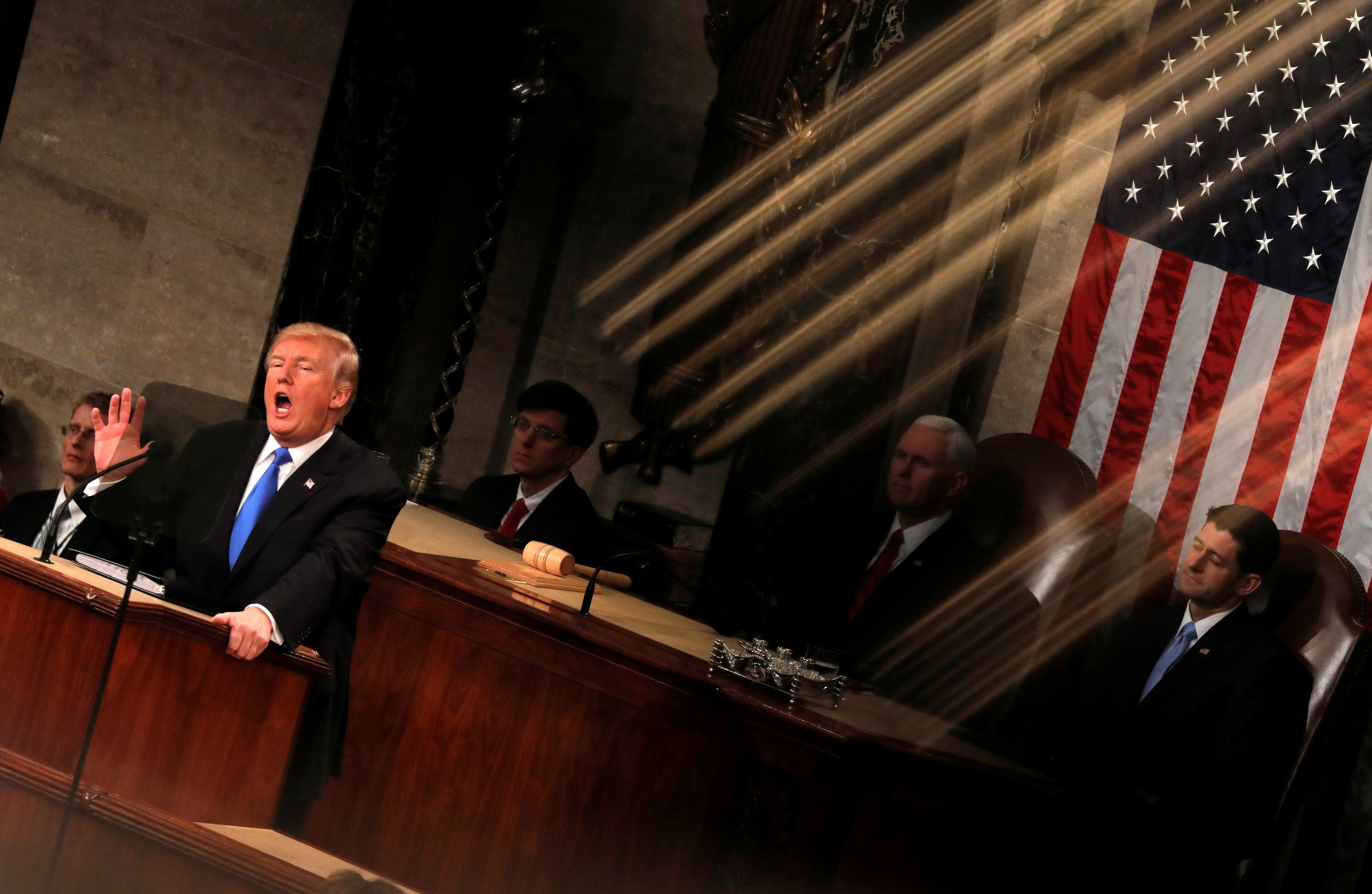 U.S. President Donald Trump and Vice President Mike Pence (C) are seen behind the reflection of a House chamber railing as Trump delivers his State of the Union address to a joint session of the U.S. Congress on Capitol Hill in Washington, U.S. January 30, 2018. REUTERS/Carlos Barria     TPX IMAGES OF THE DAY