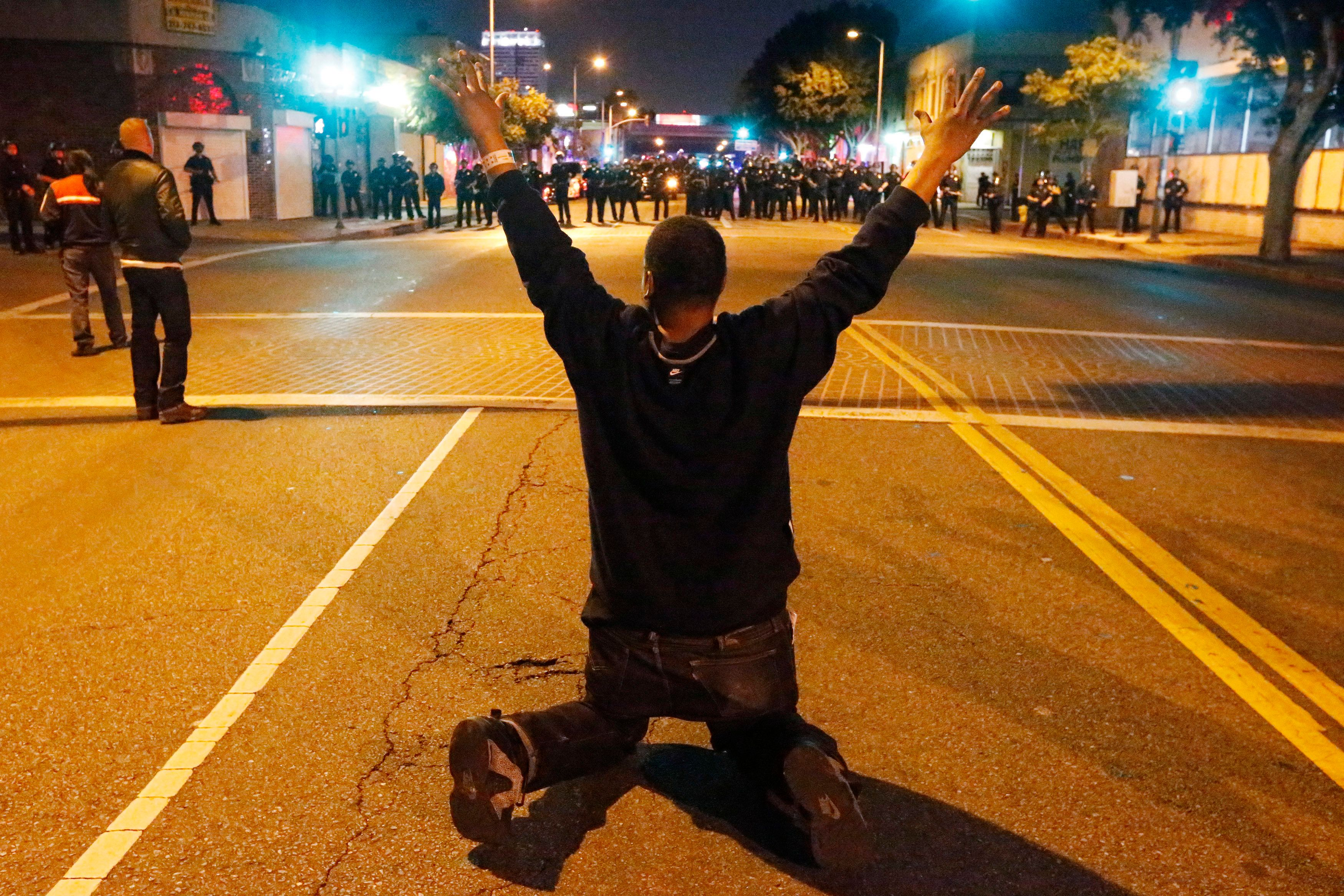A man kneels in the road in front of a line of police during a demonstration in Los Angeles, California November 24, 2014, following the grand jury decision in the shooting of Michael Brown in Ferguson, Missouri. REUTERS/Lucy Nicholson   (UNITED STATES - Tags: CIVIL UNREST CRIME LAW)