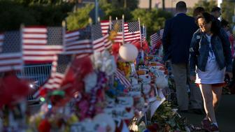 """Terri Xiang of Texas looks over 58 wood crosses, with the names and photos of the October 1 mass shooting victims, in the median of Las Vegas Boulevard South near the """"Welcome to Las Vegas"""" sign in Las Vegas, Nevada U.S. October 9, 2017. REUTERS/Las Vegas Sun/Steve Marcus"""