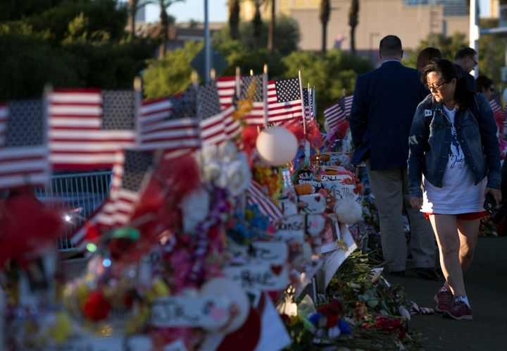 Terri Xiang of Texas looks over 58 wood crosses with the names and photos of the Las Vegas shooting victims.