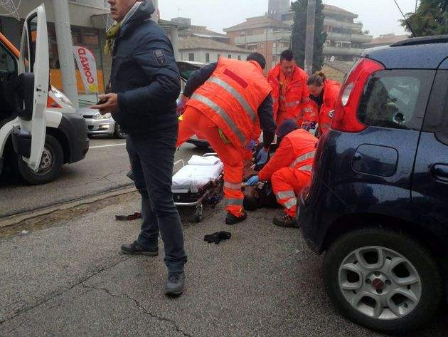 Paramedics treat an injured personwho was shot from a passing vehicle in Macerata,