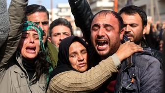 A picture taken on February 3, 2018, in the town of Afrin shows the mother (C), brother (R) and sister (L) of the late 23-year-old YPJ fighter Barin Kobani, attending a mourning ceremony in her honor, after the YPJ and the Syrian Observatory for Human Rights accused Turkish-backed Syrian rebels of filming her mutilated dead body. / AFP PHOTO / Delil souleiman        (Photo credit should read DELIL SOULEIMAN/AFP/Getty Images)