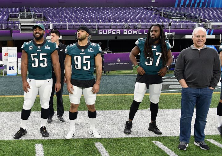 Brandon Graham #55, Mychal Kendricks #95 and Dannell Ellerbe #57 of the Philadelphia Eagles look on with team owner Jeffrey L